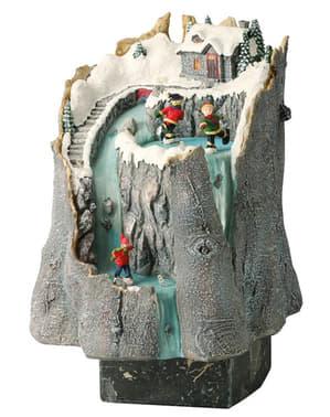 Villaggio natalizio in miniatura con casa in montagna con luci e movimento
