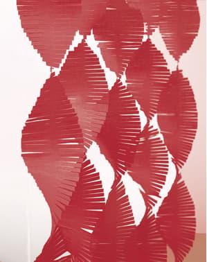 Punainen tupsuverho kreppipaperista