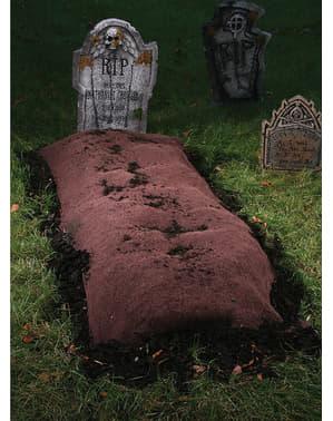Tyg med uppgrävd jord för grav