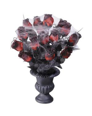 Maljakko jossa punaisia ruusuja ja hämähäkinseittiä