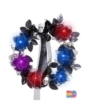 Blomkrans med dödskallar, svarta blommor och skimrande ljus
