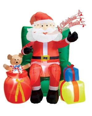 Puhallettava joulupukki istumassa jättinojatuolilla