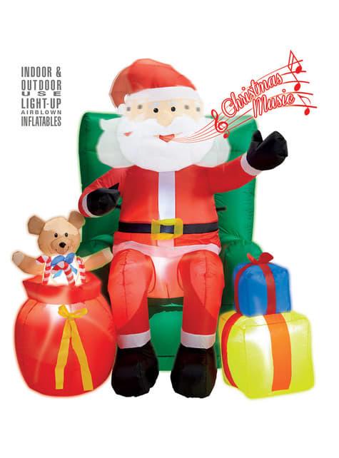 Figura decorativa de Pai Natal sentado sobre sofá gigante