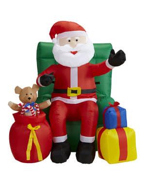 Gigantisk uppblåsbar jultomte sittandes i fotölj