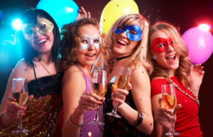 Portrait of happy young girls under masks on the party